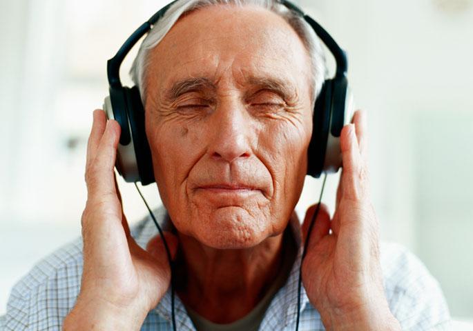 älterer Mann mit modernen Kopfhörern in Musik vertieft