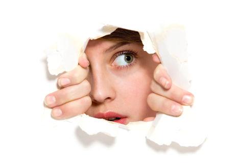 Frau blickt durch Loch in Papierwand
