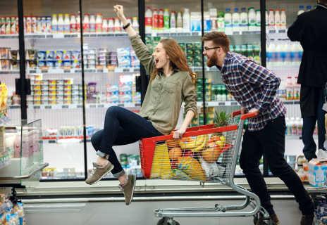 Junges Paar im Supermarkt - die Frau sitzt im Einkaufswagen