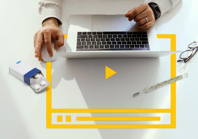 Person am Notebook mit Tabletten, Fieberthermometer und Brille