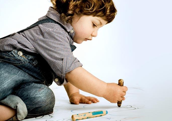 Kleinkind malt mit dicken Stiften auf dem Boden