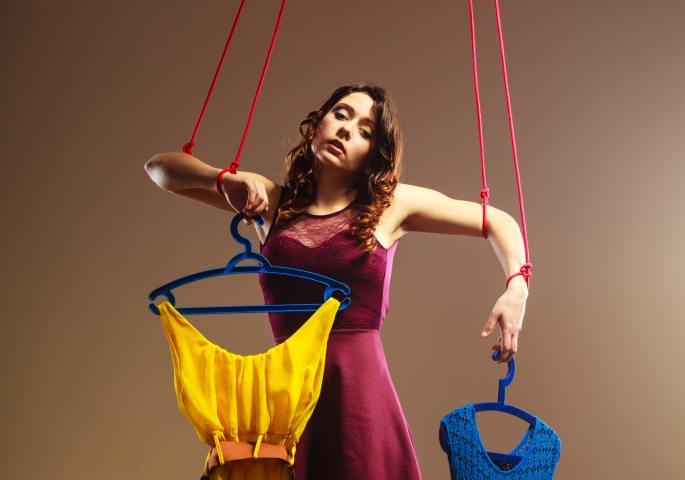 Frau als Marionette mit Kleidungsstücken in den Händen