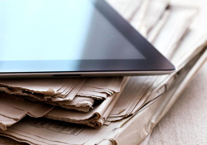 Tablet und Zeitungsstapel