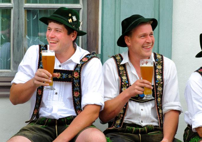 Bayerische Männer in Tracht mit Weizenbier