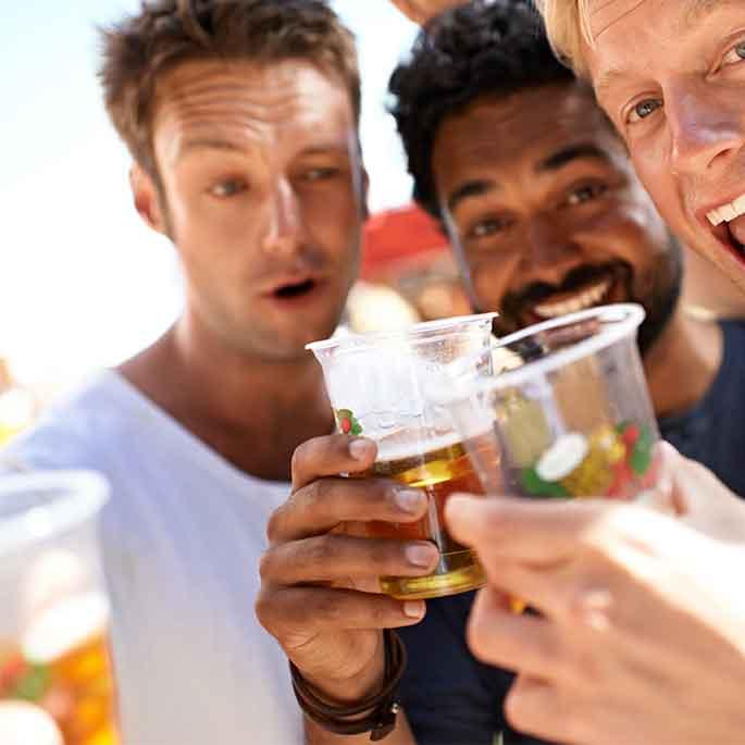 Junge Männer auf einem Festival trinken Bier aus Plastikbechern