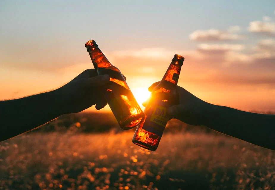 Beerflaschen anstossen bei Sonnenuntergang