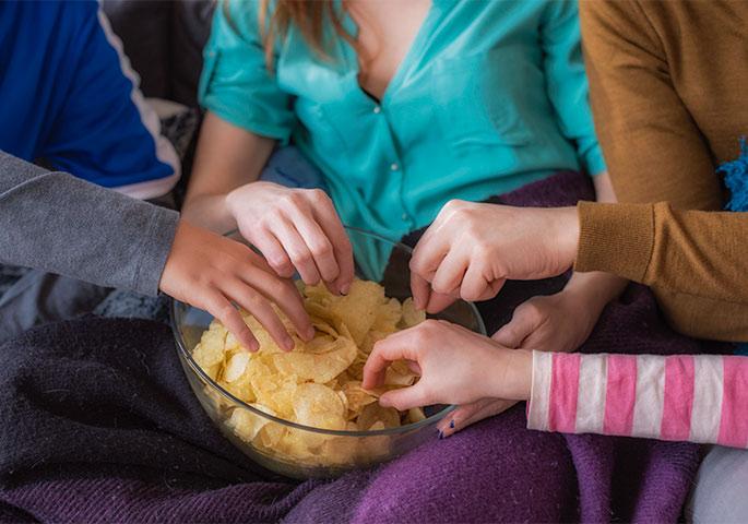 Mehrere Hände greifen in Schüssel mit Chips.
