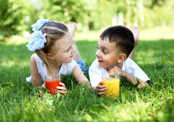 Kinder liegen mit Getränk in Wiese.