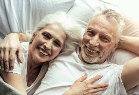 Älteres Paar liegt zusammen strahlend im Bett