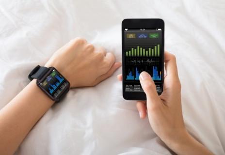 Mann überprüft Daten seiner Smartwatch mit dem Handy