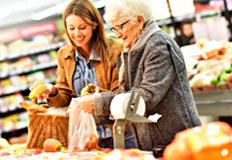 Junge und ältere Frau lachend in der Obst- und Gemüseabteilung eines Handelsgeschäfts.