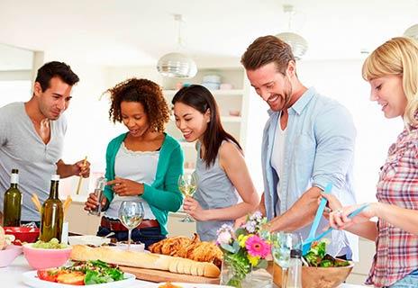 Eine Gruppe junger fröhlicher Menschen kocht zusammen.